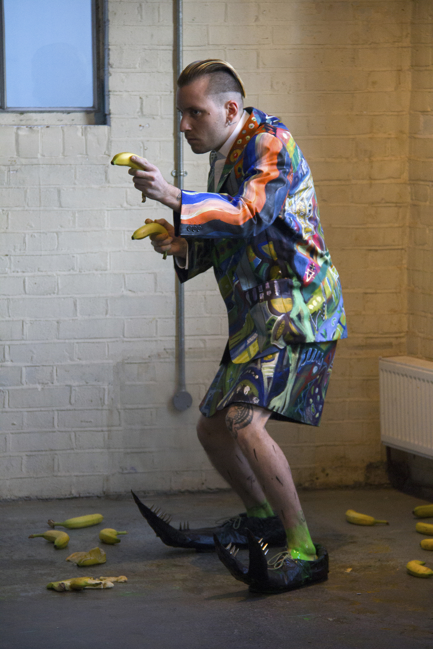 Male identified person holding two bananas as if they were guns. Image reference Andy Warhol Elvis.