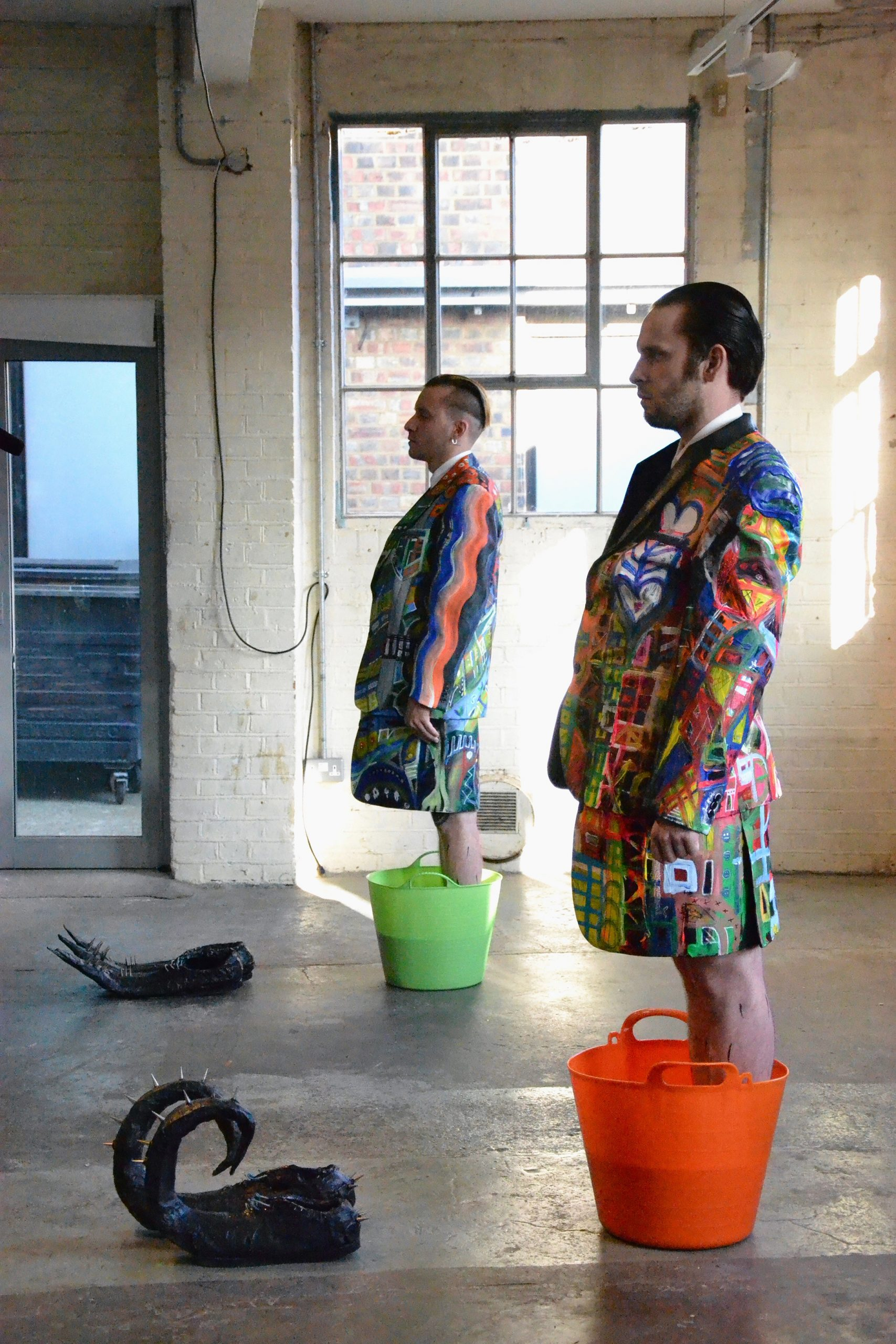 Two male identified people standing inside buckets full of fluorescent paint, in front of them two pairs sculptural shoes known as unidentified performing objects by Luca Bosani