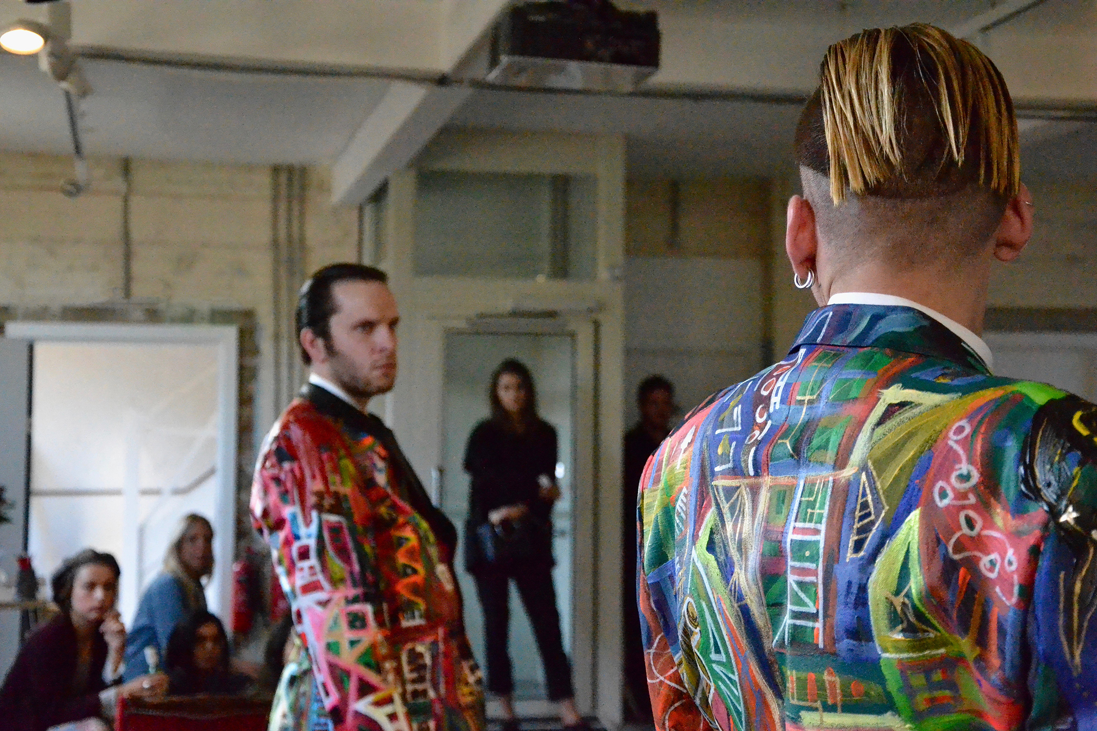 Two male identified characters stare in each other eyes wearing an extremely colourful jacket