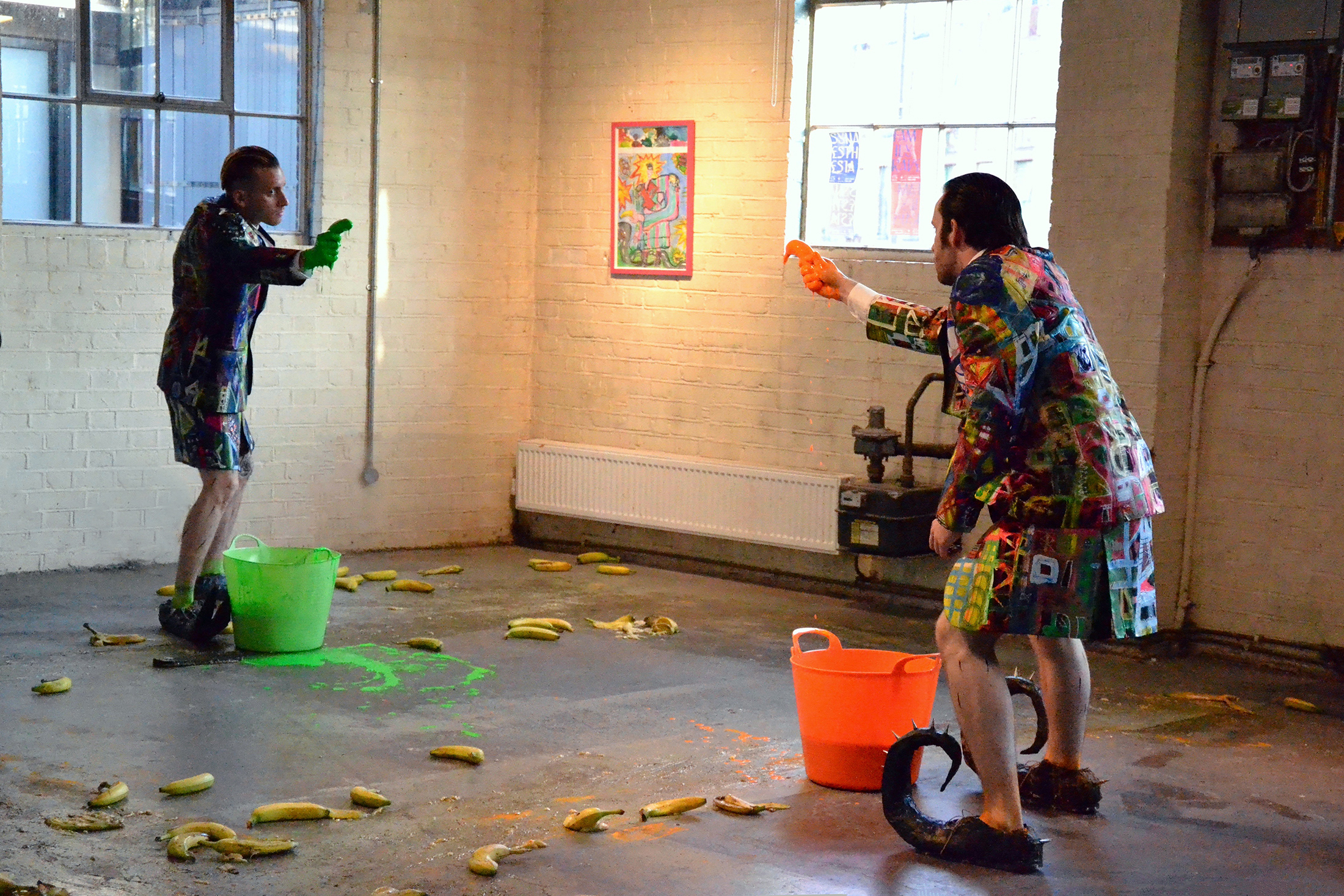 Two men pointing two bananas against each other as if they were guns. Image reference Andy Warhol Elvis. Bananas on the floor, fluorescent paint spilled on the ground.
